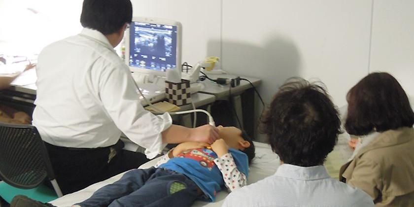 両親が見守るなか、甲状腺検診を受ける男の子(パルシステム東京)