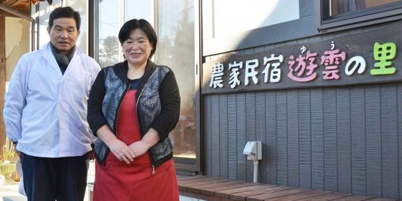 「農家民宿遊雲(ゆう)の里」の前に立つ菅野正寿さん、まゆみさん夫妻(写真=編集部)