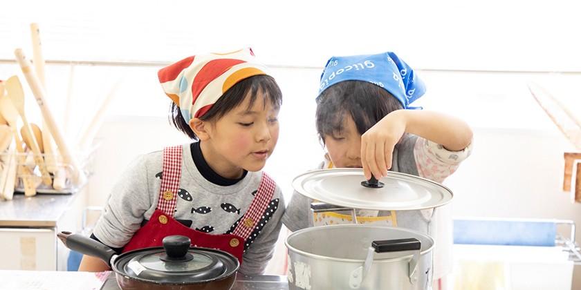 鍋のふたをおそるおそる開けて、中の様子を見る二人の子ども