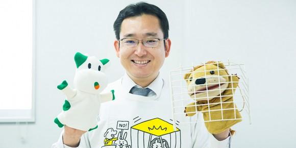 弁護士の楾大樹先生が、ライオンとパルシステムのキャラクター「こんせんくん」の人形を手にはめ、笑顔で憲法を解説