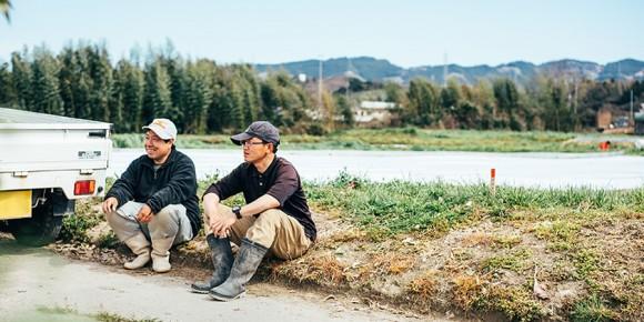 畑でほほ笑む2人の男性