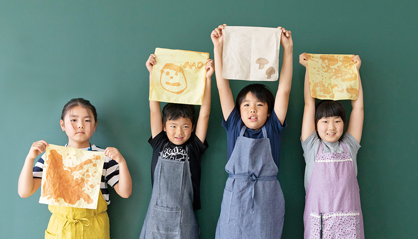 のこり染ワークショップに参加した子どもたちが自分で染めたハンカチを持ってポーズとる様子
