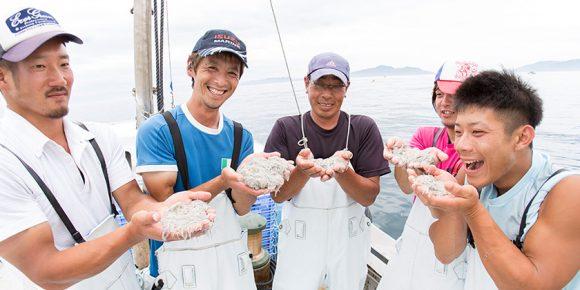 船の上で、とれたての生しらすを手に笑顔を見せる若手漁師たち。