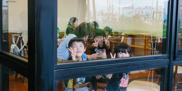 ガラス張りの食堂から外を見る子どもたち