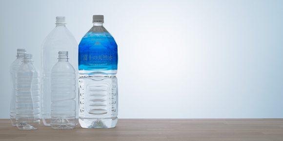 ペットボトル水「富士の天然水」と使用済みペットボトルを圧縮したかたまりがいくつも積み上げられているようす。