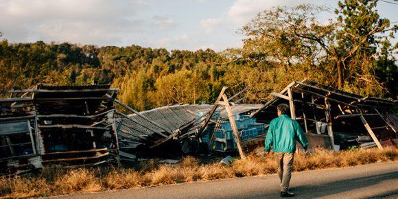 台風によって吹き飛ばされた資材小屋を眺める、菜の花エッグの梅原さん