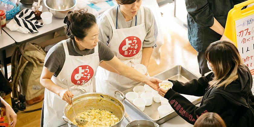 生徒に温かい麻婆豆腐を手渡すスタッフ