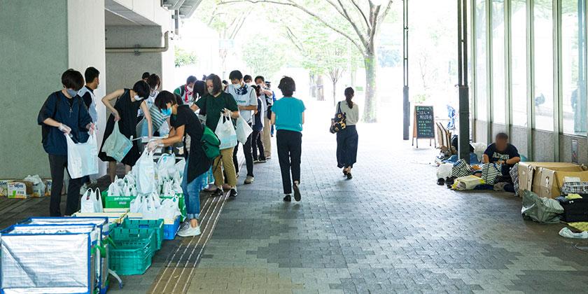 都庁下の歩道で配付する食品を袋に詰めるボランティアの人々