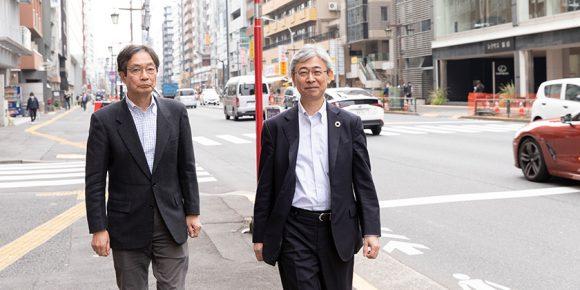 車が行き来する街中を背景に、二人の男性が歩道を歩いている。
